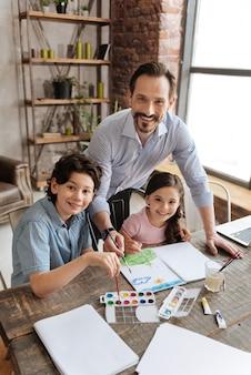 幼い娘の後ろに立って絵に手を伸ばし、息子がパレットから紫色を選んでいる間、いくつかのストロークをしたいハンサムな魅力的な父親