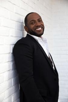 고급스러운 검은 양복을 입은 잘생긴 쾌활한 아프리카계 미국인 사업가