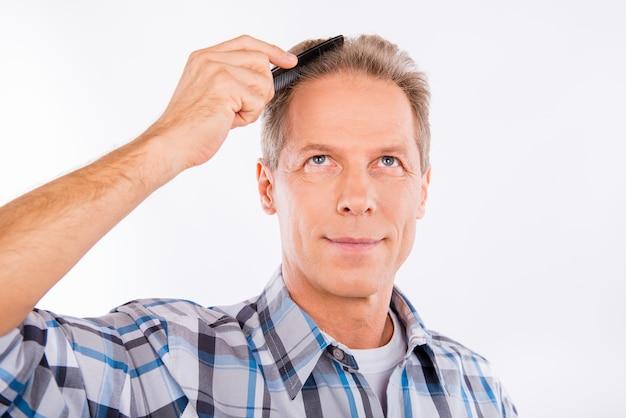 Красивый веселый пожилой мужчина расчесывает волосы