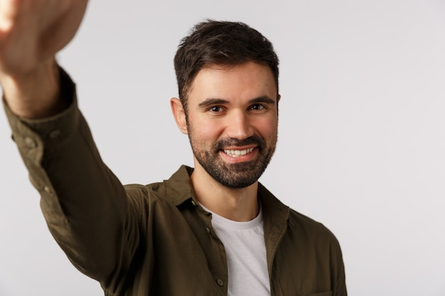 Handsome cheerful bearded man in coat want upload new photo gay dating application, hold smartphone with arm and smiling camera, taking selfie, standing joyful
