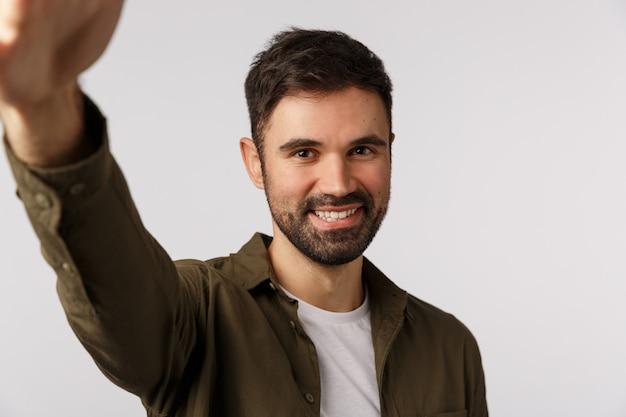Красивый веселый бородатый мужчина в пальто хочет загрузить новое фото приложение для знакомств геев, держать смартфон с рукой и улыбаться в камеру, принимая селфи, стоя радостное