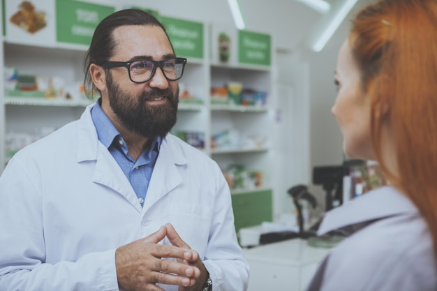 Handsome cheerful bearded pharmacist talking to a customer at drugstore