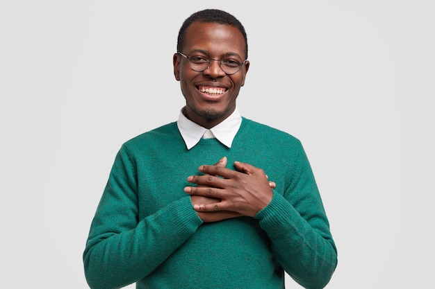 Handsome cheerful black man keeps both hands on chest, feels touched or thankful, smiles broadly, wears elegant green sweater