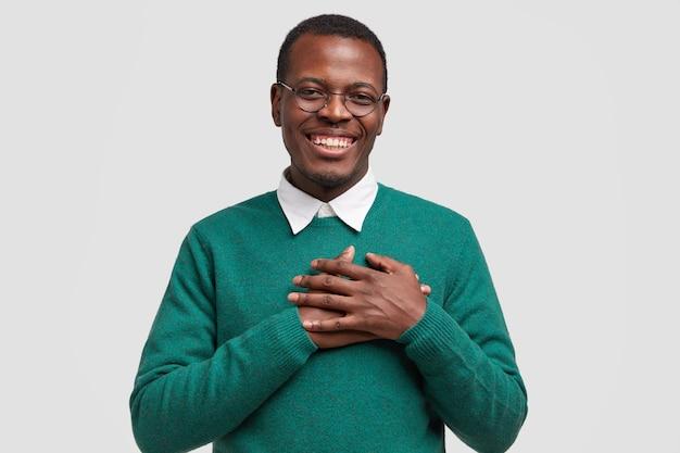 ハンサムな陽気な黒人男性は両手を胸に保ち、触れられたり感謝したりし、広く笑顔で、エレガントな緑のセーターを着ています