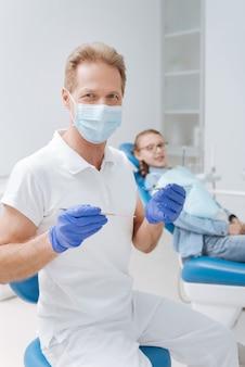 전문 장비를 사용하고 작은 환자를위한 상담을 개최하는 동안 잘 생긴 쾌활한 유능한 의사가 작업 과정에 참여하고 있습니다.