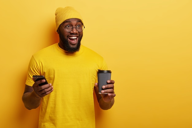 Handsome cheerful dark skinned guy with thick bristle, has fun indoor, holds cellular, waits for call, enjoys drinking hot beverage, isolated over yellow wall. people, technology concept