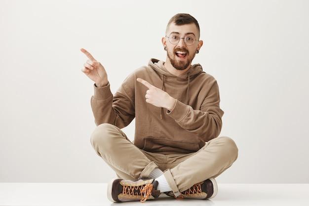 Bel ragazzo allegro puntare il dito a sinistra e sedersi sul pavimento