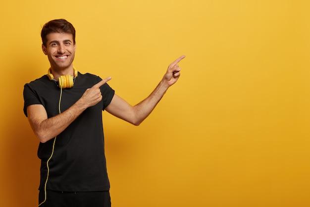 검은 옷을 입고 복사 공간에서 잘 생긴 쾌활한 남자 포인트, 헤드셋을 착용하고, 이빨 미소 짓고, 노란색 배경 위에 고립 된 광고를 보여줍니다.
