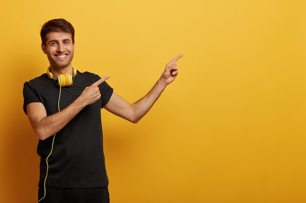 Handsome cheerful man points at copy space, dressed in black clothes, wears headset, smiles toothily, demonstrates advertisement, isolated over yellow background