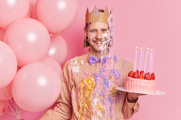 Handsome cheerful man stands dirty with cream holds delicious strawberry cake celebrates birthday stands with holiday attributes isolated over pink wall