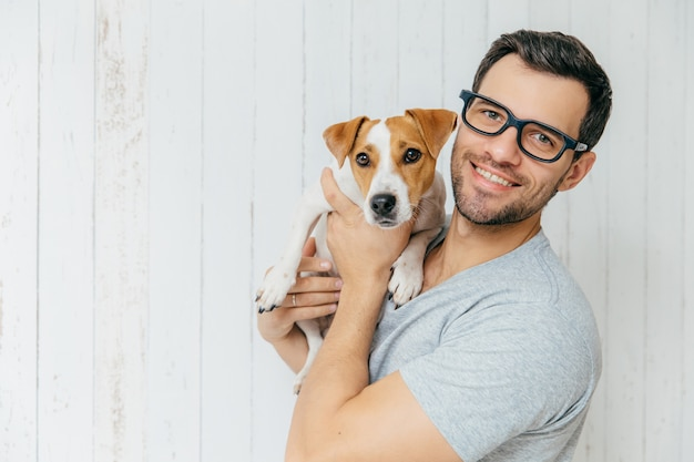 Handsome cheerful man, wears eyeglasses, holds jack russell terrirer, has glad expression, poses against white wooden wall