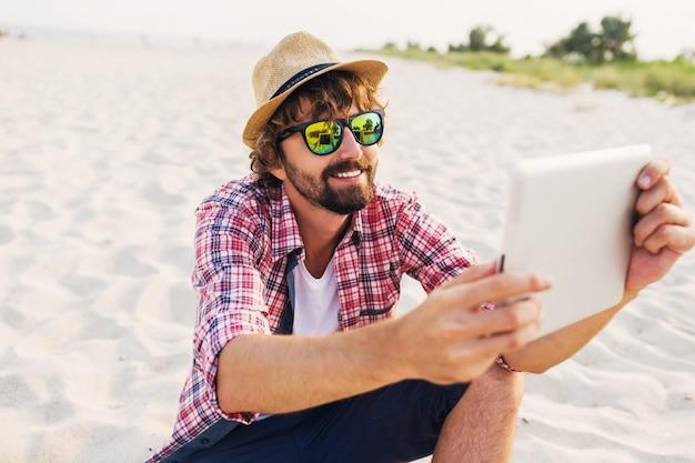 Bell'uomo allegro con la barba in cappello di paglia, camicia a scacchi e occhiali da sole alla moda che si siede sulla sabbia bianca e utilizzando tablet