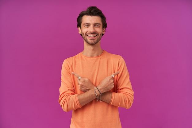 갈색 머리와 강모와 잘 생기고 쾌활한 남자. 주황색 스웨터를 입고. 팔찌와 반지 있음