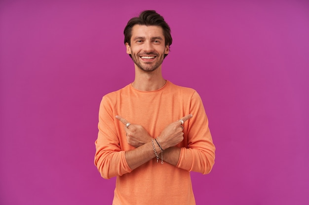 Uomo bello e allegro con capelli castani e setole. indossare un maglione arancione. ha bracciali e anelli
