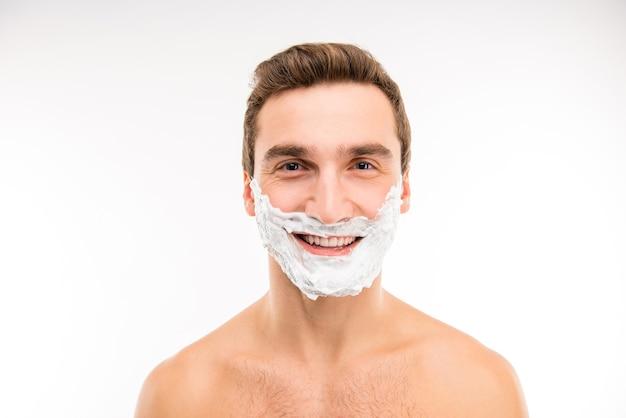 Красивый веселый мужчина с пеной для бритья на лице