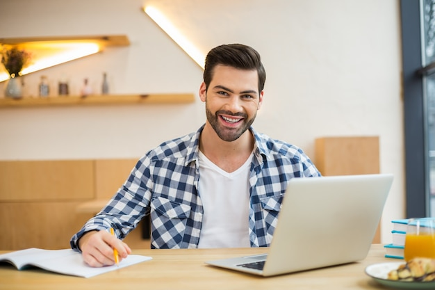 Handsome cheerful nice man sitting in front of his laptop and smiling while working in the office