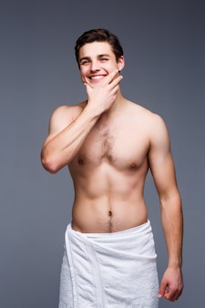 Handsome cheerful shirtless man posing in white towel isolated on grey wall