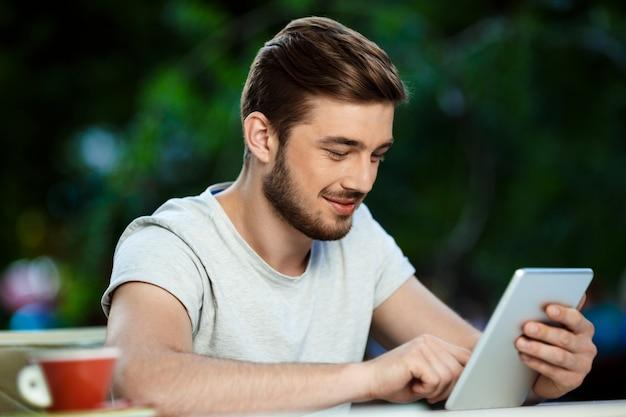 Giovane sorridente allegro bello che si siede al tavolo in compressa all'aperto della tenuta del caffè che guarda sullo schermo.