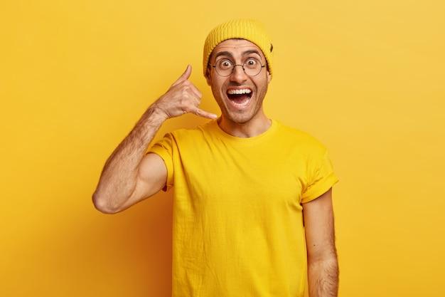 ハンサムで陽気なおしゃべりな男は私をジェスチャーと呼び、腕を耳に上げ、電話で話しているふりをします
