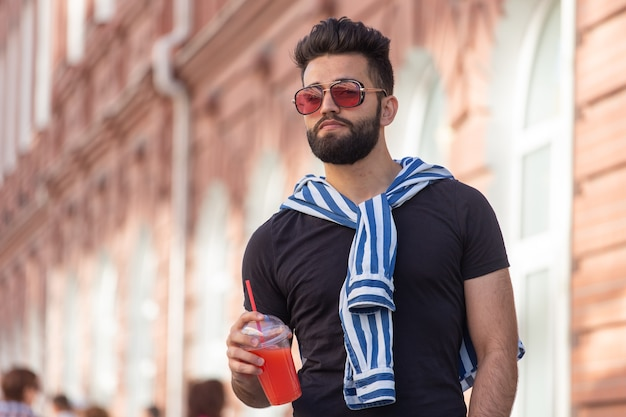 Handsome cheerful young arabian student with a stylish mustache and a beard with juice in his hands, walking around the city after a working day. concept of positive and rest.