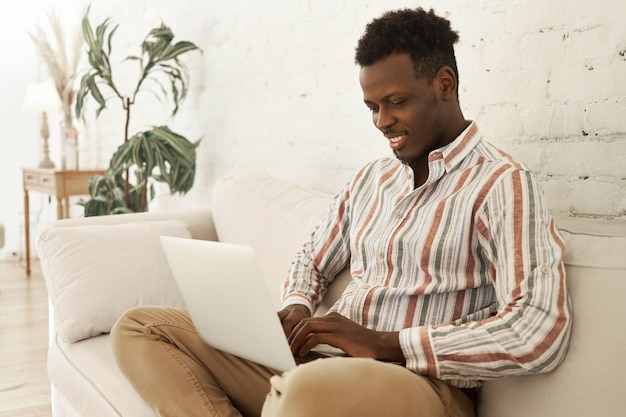 Handsome cheerful young dark skinned male smm manager enjoying working from home sitting on sofa with laptop computer