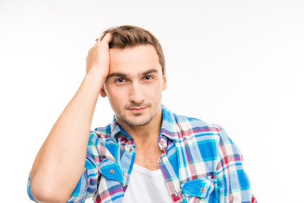 Красивый веселый молодой человек, расчесывающий волосы пальцами