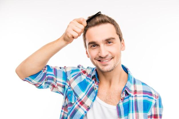 Красивый веселый молодой человек, расчесывающий волосы