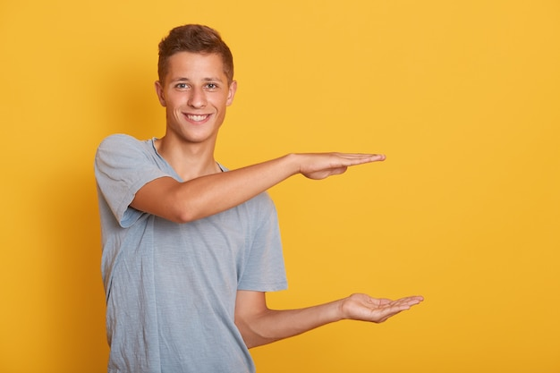 Handsome cheerful young man making gesture, showing measure