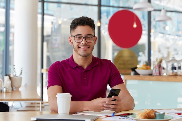 Handsome cheerful young man searches job, browses webpage on modern cell phone, checks information in internet, sits at cafeteria, enjoys sweet dessert and fresh drink
