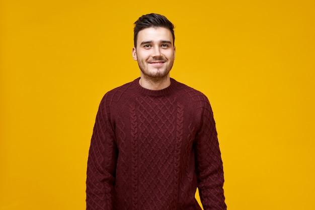 Bel giovane allegro con taglio di capelli alla moda e sorriso increspato in posa isolata contro il muro giallo vuoto, vestito con un maglione marrone rossiccio accogliente, con un aspetto fiducioso