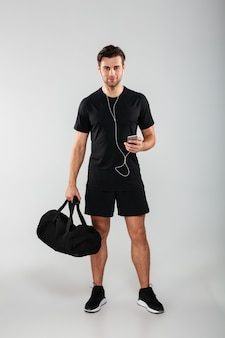 Handsome cheerful young sports man using phone listening music