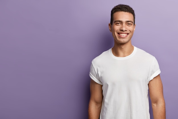 Handsome cheerful young sportsman has sporty body, muscular arms, wears white mock up t shirt, has short dark hair, toothy appealing smile, stands over purple wall, blank copy space aside