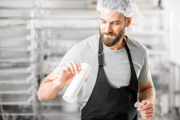 Handsome cheese maker checking quality of a cheese working at the small producing farm