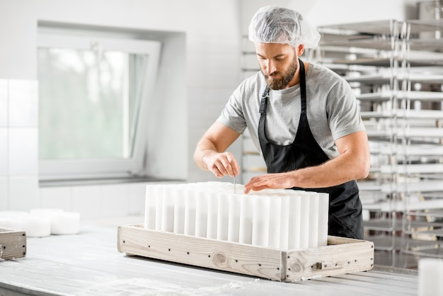 Handsome cheese maker in uniform forming cheese into molds at the small producing farm