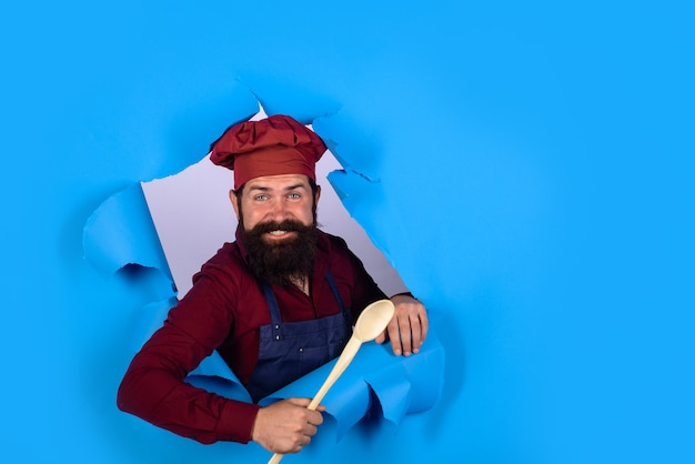 Handsome chef cook with wooden spoon looking through paper chief man in cook uniform holds wooden