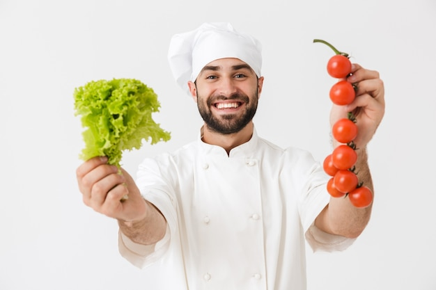 Handsome chef man in cook hat smiling while holding tomato and salad at work isolated over white wall