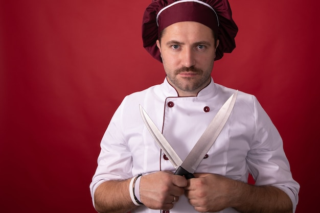 Handsome chef poses with knives in his hands