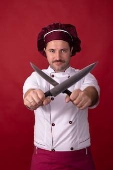 ハンサムなシェフがナイフを手にポーズをとる