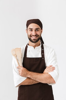 Handsome chief man in cook uniform smiling while holding wooden kitchen appliances isolated over white wall