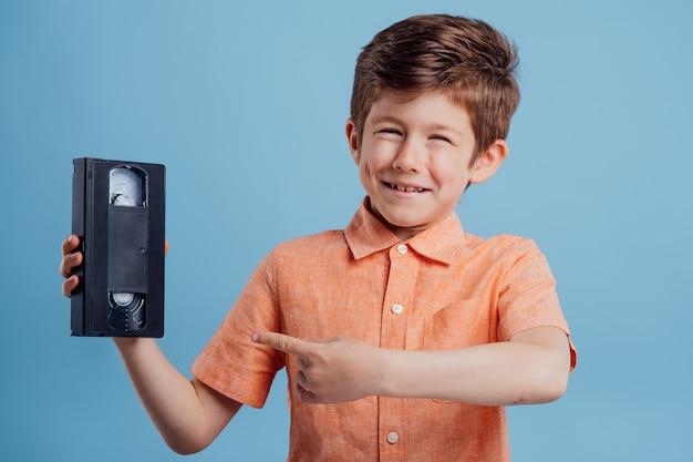 파란색 배경 poiting에 고립 된 비디오 테이프와 잘 생긴 아이