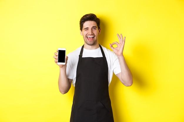 노란색 배경 위에 서있는 응용 프로그램을 추천하고 확인 서명 및 스마트 폰 화면을 보여주는 잘 생긴 커피 숍 노동자.