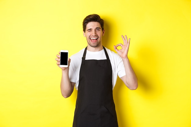 Handsome coffee shop worker showing ok sign and smartphone screen, recommending application, standing over yellow background.