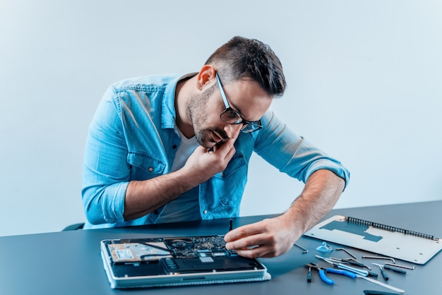 Handsome computer engineer talking on a mobile phone while repairing laptop computer.
