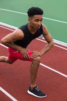 Handsome concentrated african athlete man make stretching exercises