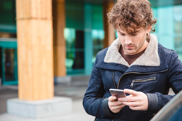 Handsome concentrated attractive thoughtful young curly man in black jacket using smartphone in the city