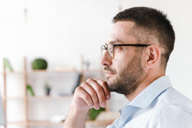 비즈니스 센터의 사무실 방에서 일하는 동안 흰색 셔츠와 안경을 착용하고 잘 생긴 집중된 남자 30 대