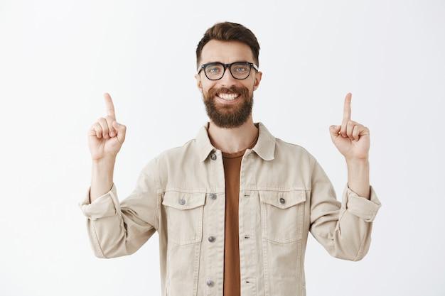 Красивый уверенный в себе бородатый мужчина в очках позирует у белой стены