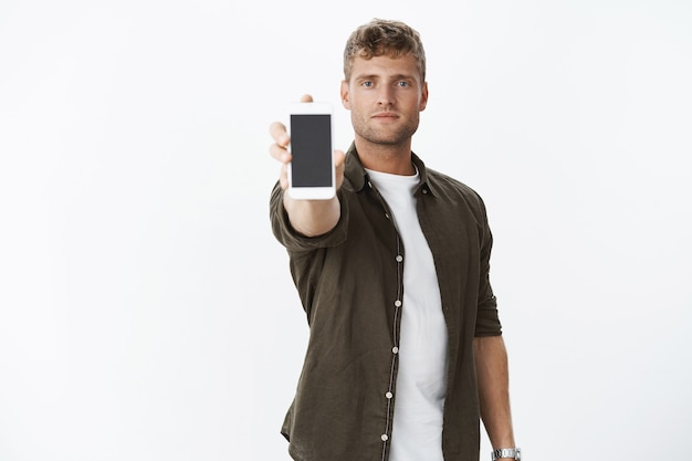 Handsome confident blond man showing you smartphone screen extending hand with mobile phone at front looking cool and chill presenting app or cellphone, standing over gray wall