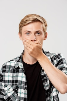 Handsome confident blond young man wearing casual plaid shirt covering mouth with hand, on grey wall