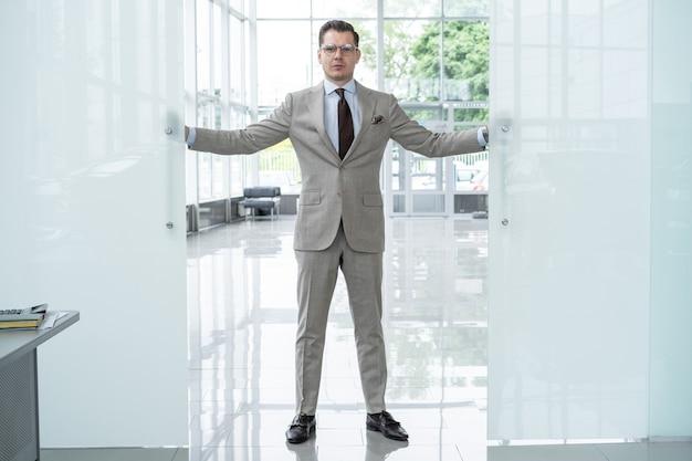 スーツを着たハンサムな自信のあるビジネスマンがオフィスに入る。